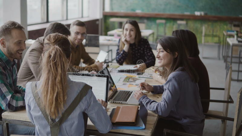 De vrouwelijke teamleider brengt documenten aan creatief commercieel team Gemengde rasgroep die mensen in modern bureau samenkome royalty-vrije stock foto