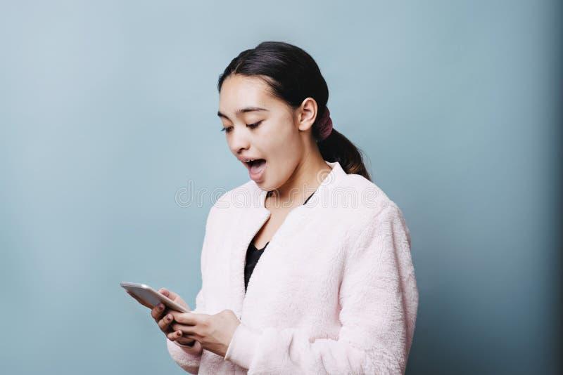 De vrouwelijke Tiener schokte terwijl het Bekijken Celtelefoon stock foto