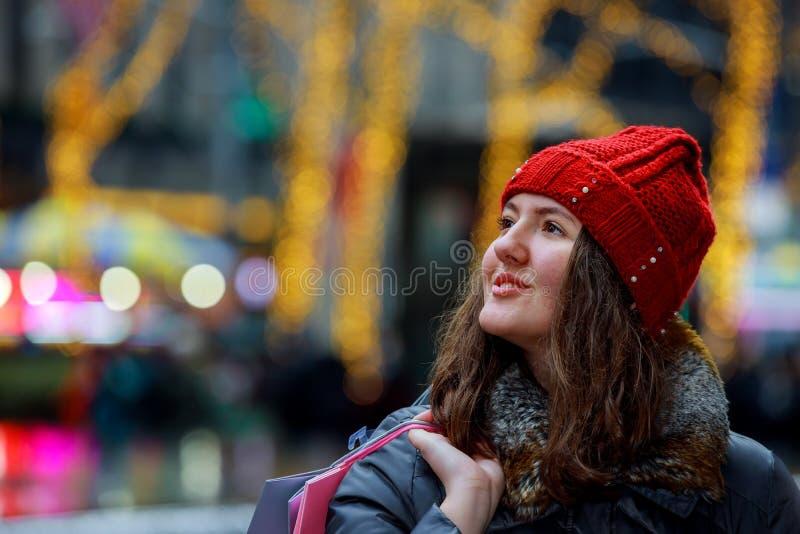 De vrouwelijke tienerhanden die het winkelen houden doet, kleurrijke lichten bokeh in zakken royalty-vrije stock foto's