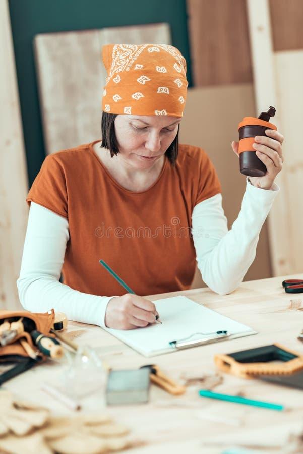 De vrouwelijke timmerman drinkt koffie en plant DIY project stock afbeeldingen