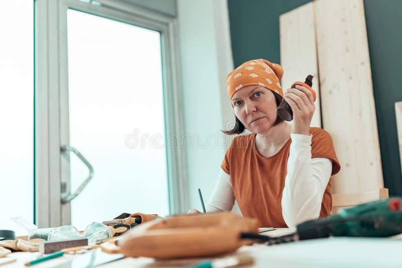 De vrouwelijke timmerman drinkt koffie en plant DIY project stock fotografie