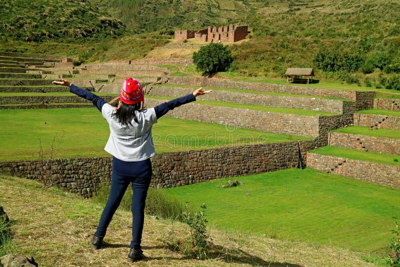 De vrouwelijke toerist die haar wapens voelen opheffen geïmponeerd met Inca stapte landbouwruïnes van de archeologische plaats va royalty-vrije stock foto's