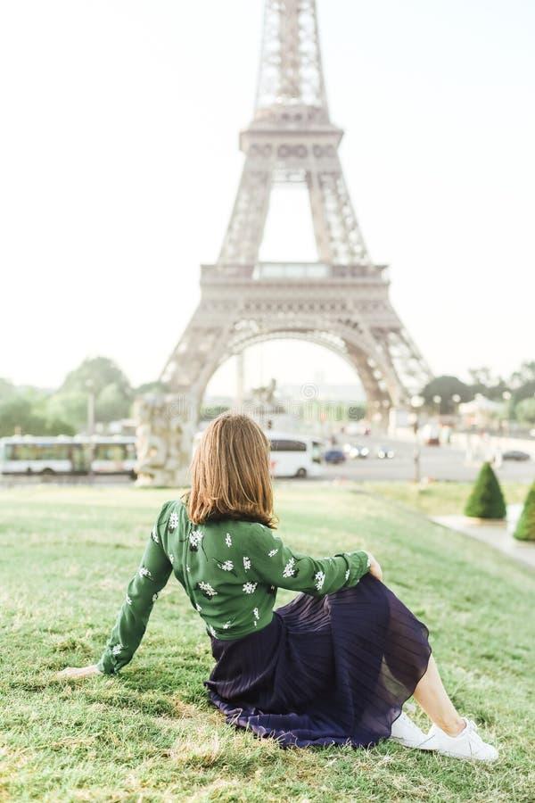 De vrouwelijke toerist kijkt de rug van de de torenzitting van Eiffel stock afbeelding