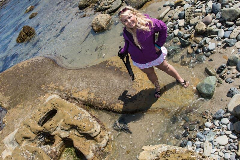 De vrouwelijke toerist vindt het interessante overzeese die leven omhoog op de stranden bij het Nationale Monument van Puntcabril royalty-vrije stock afbeelding