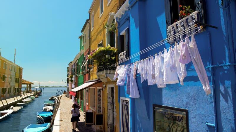 De vrouwelijke toeristen gaan winkelend in kleurrijke straat van Burano-eiland in de Lagune van Venetië stock fotografie
