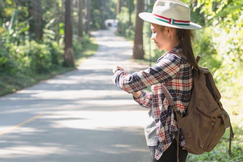 De vrouwelijke toeristen met rugzakken wachten op bussen in het platteland met bomen en mooie aard stock foto's