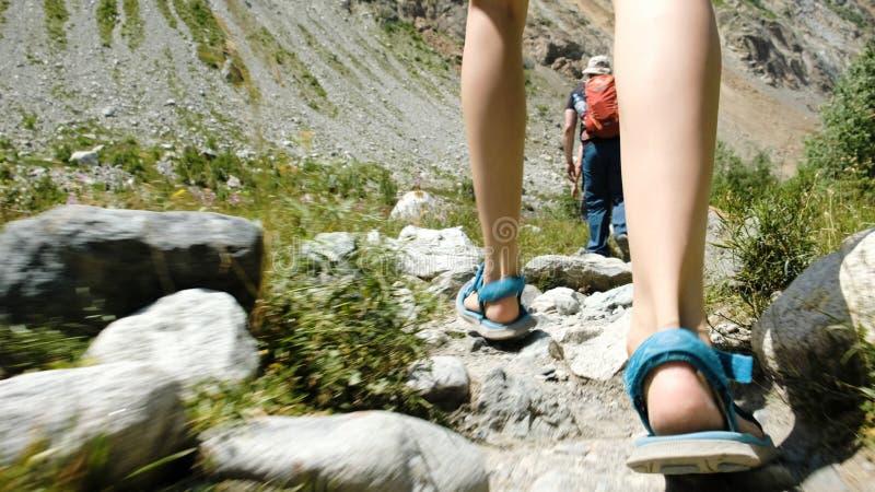 De vrouwelijke toeristenbenen in wandelingssandals zijn op de route royalty-vrije stock foto's