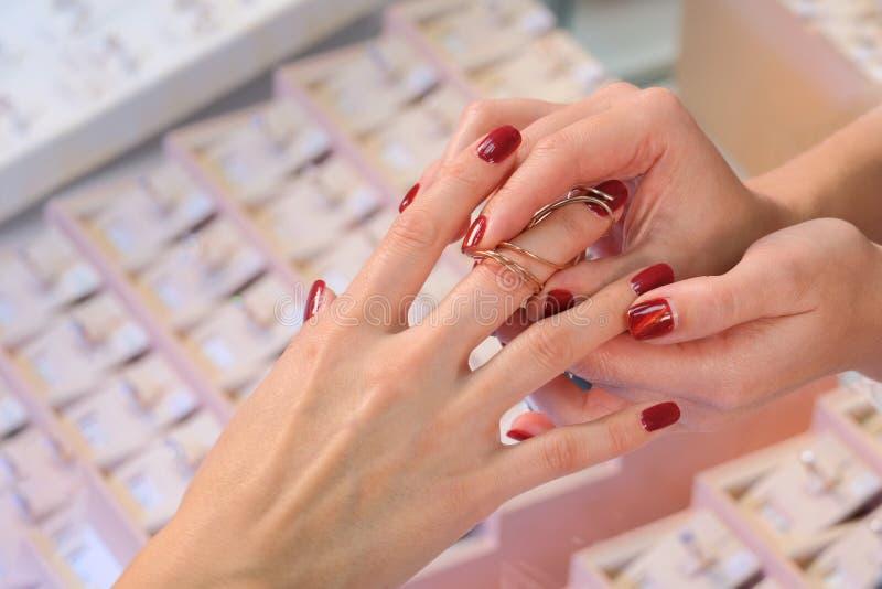De vrouwelijke verkoper in een opslag van luxejuwelen stelt een ring voor Het kopen en het winkelen Vrouwenjuwelier royalty-vrije stock afbeeldingen
