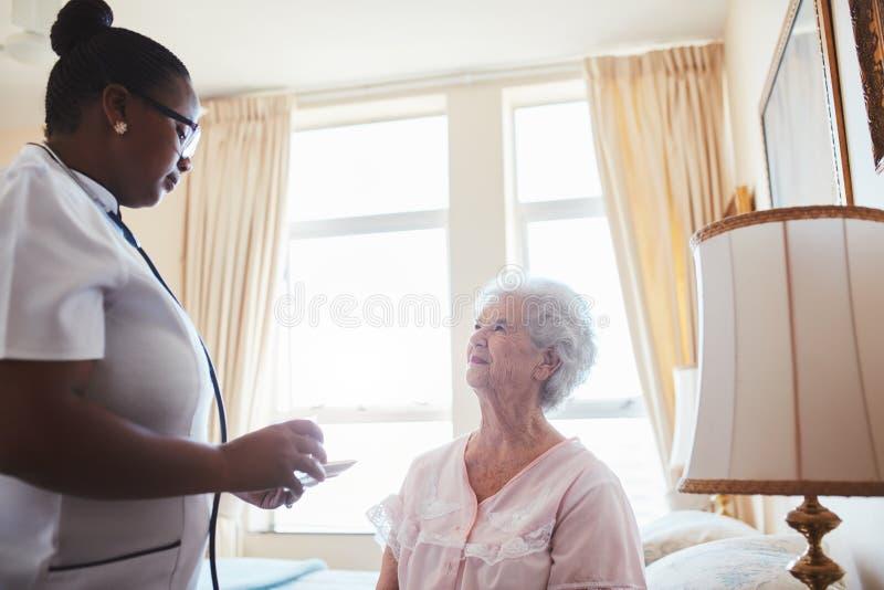 De vrouwelijke verpleegster staat een bejaarde vrouwelijke patiënt met geneesmiddelen bij stock afbeeldingen