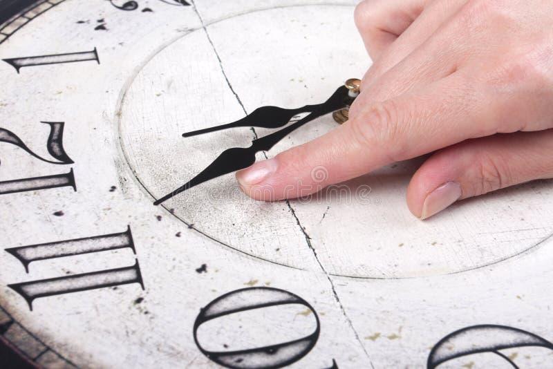 De vrouwelijke vinger verandert de tijd op een klok royalty-vrije stock afbeelding