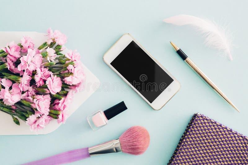De vrouwelijke vlakte legt op blauwe achtergrond, hoogste mening van vrouwen` s Desktop met envelop, bloemen, pen, blocnote en sm royalty-vrije stock fotografie