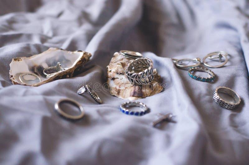 De vrouwelijke vlakte legt van ringen aan vingers in shells van oesters stock fotografie