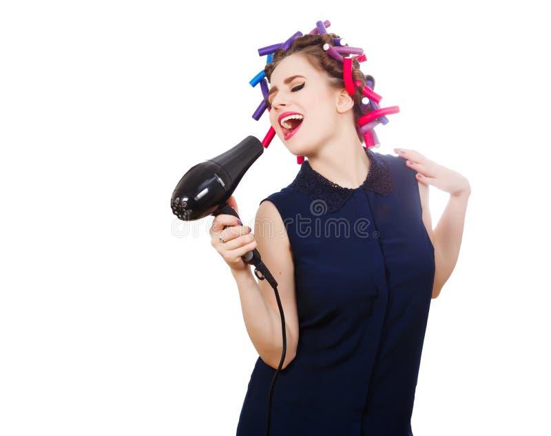 De vrouwelijke vocalist in krulspeld gebruikt hairdryer als microfoon stock foto's