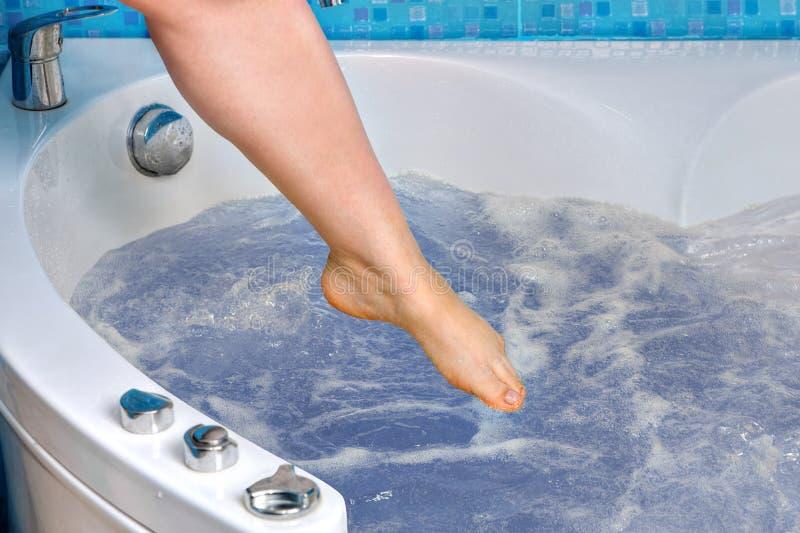 De vrouwelijke voet daalt in het massagebad, close-up stock fotografie