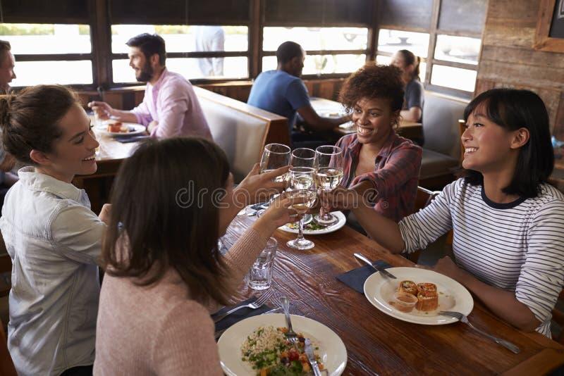 De vrouwelijke vrienden die een toost maken bij een restaurant, sluiten omhoog stock fotografie