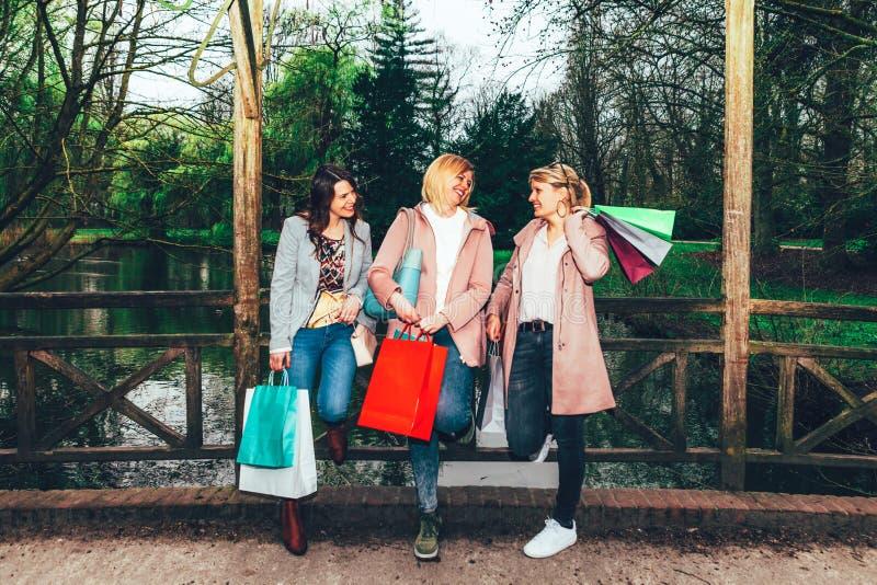 De vrouwelijke vrienden groeperen samen het hebben van pret bij het stadspark na het winkelen stock afbeeldingen
