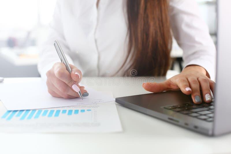 De vrouwelijke wapens schrijven met zilveren pen en type bij laptop stock fotografie