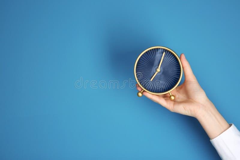 De vrouwelijke wekker van de handholding op kleurenachtergrond Het Concept van het tijdbeheer stock foto's