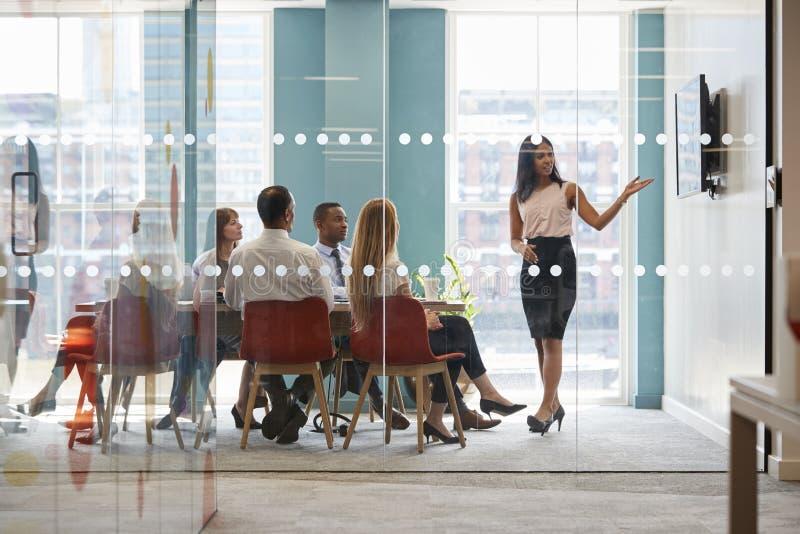 De vrouwelijke werkgever toont presentatie op het scherm op commerciële vergadering stock afbeelding