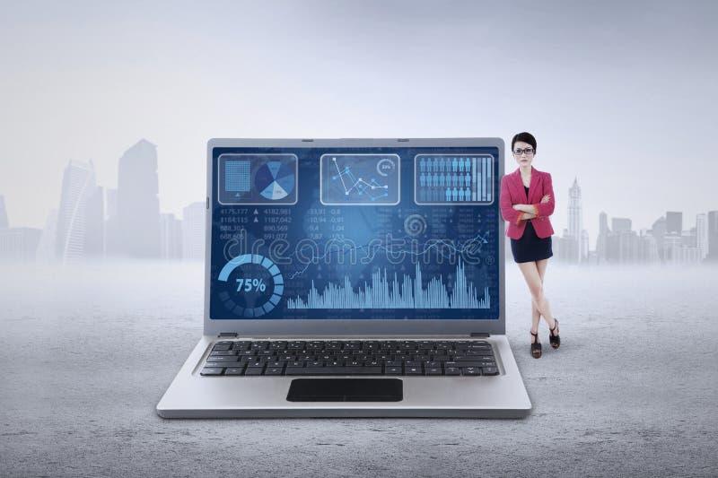 De vrouwelijke werknemer leunt op laptop met grafiek royalty-vrije stock afbeelding
