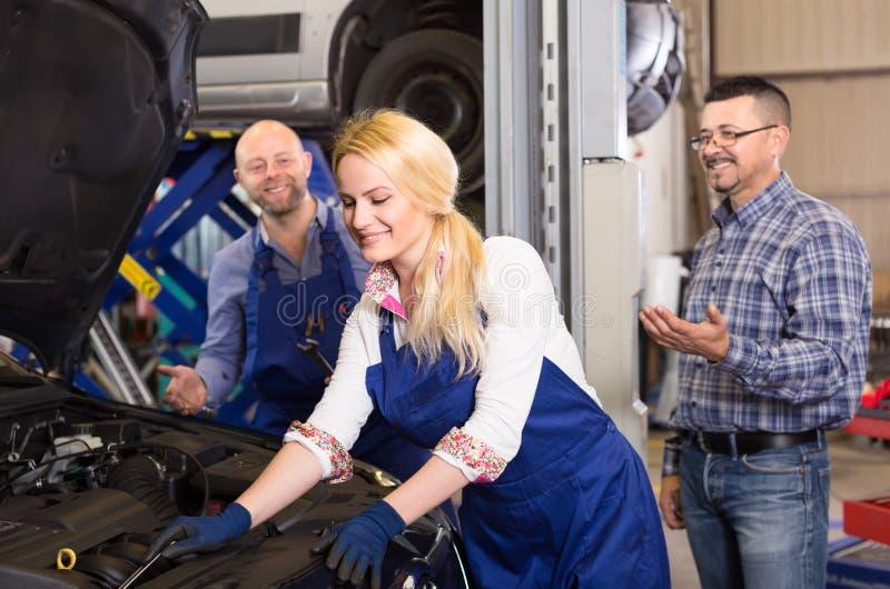De vrouwelijke werktuigkundige bevestigt een auto royalty-vrije stock afbeelding