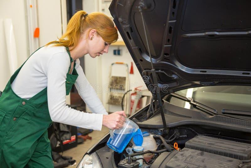 De vrouwelijke werktuigkundige vult koelmiddel of koelvloeistof in motor van een auto stock foto