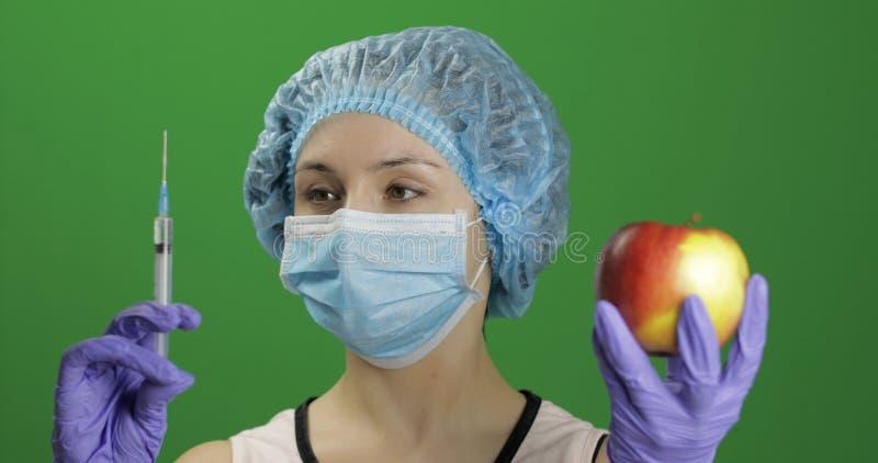 De vrouwelijke wetenschapper kiest spuit met geneesmiddelen of een appel stock foto's