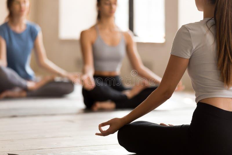 De vrouwelijke yogaleraar mediteert met studenten in lotusbloempositie stock foto
