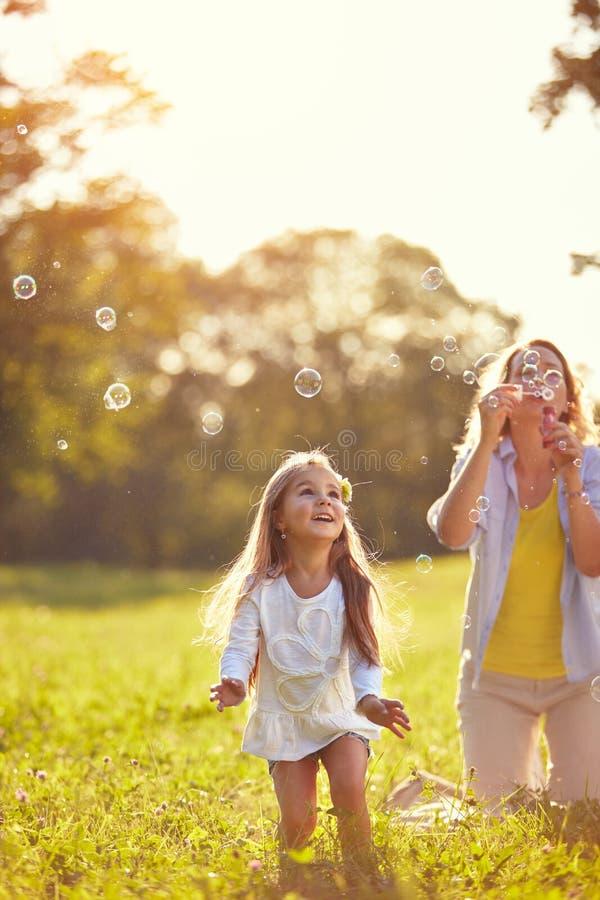 De vrouwelijke zeepbels van de kindjacht stock afbeelding