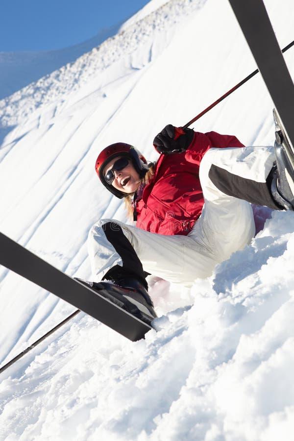 De vrouwelijke Zitting van de Skiër in Sneeuw met na Daling stock fotografie