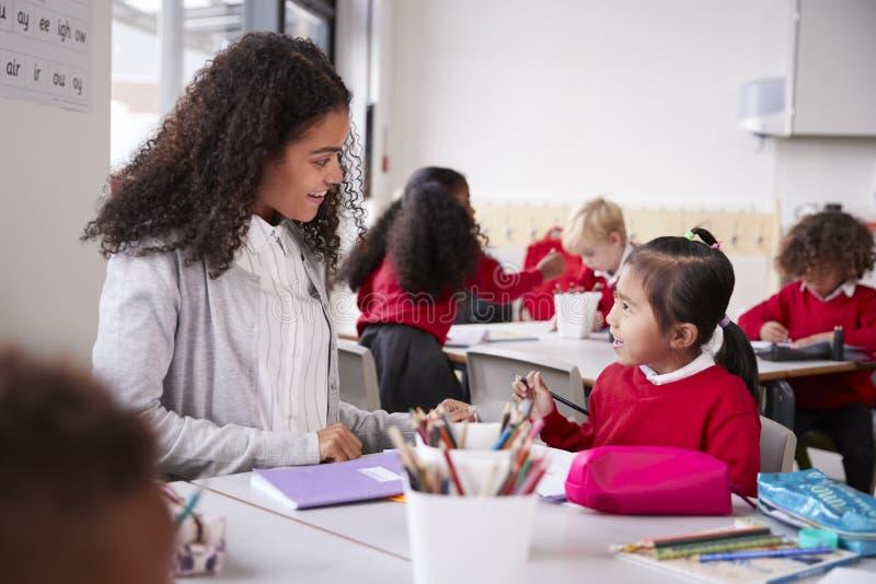 De vrouwelijke zitting van de kleuterschoolleraar bij lijst in een klaslokaal die aan een jong Chinees schoolmeisje spreken, slui royalty-vrije stock afbeeldingen