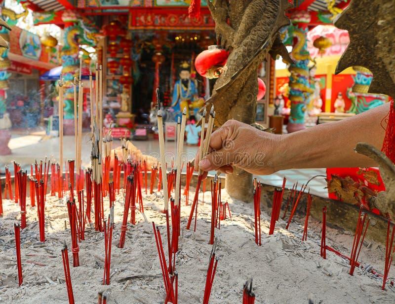 De vrouwen bidden aan Chinese goden door wierookstokken bij het heiligdom royalty-vrije stock afbeeldingen