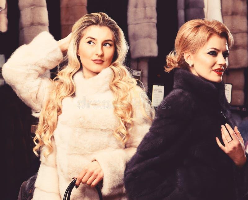 De vrouwen in bontjassen met zakken in bont winkelen Meisjes met geheimzinnige gezichten in de zwart-witte beurs van de bontjasse royalty-vrije stock foto's