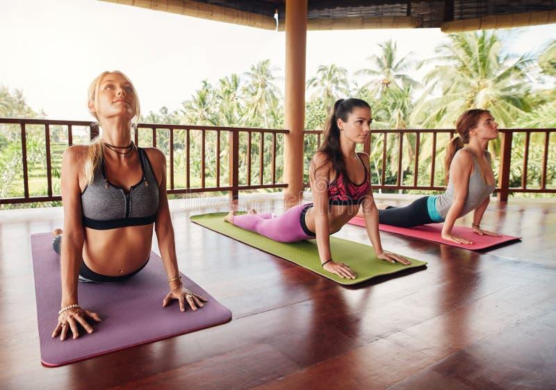 De vrouwen die cobra doen stellen op geschiktheidsmat bij gezondheidsclub royalty-vrije stock foto