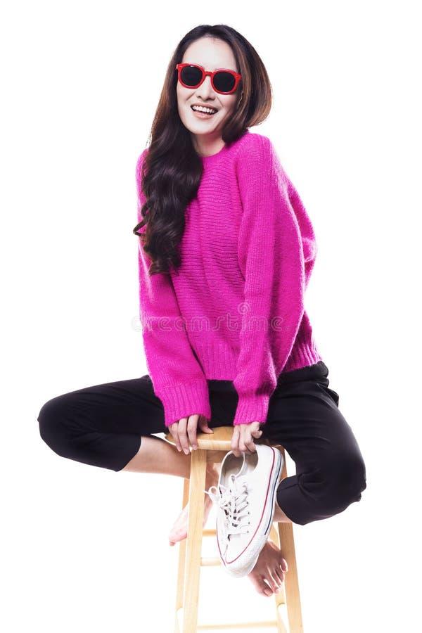 De vrouwen die een roze sweater dragen dragen sportschoffels stock fotografie