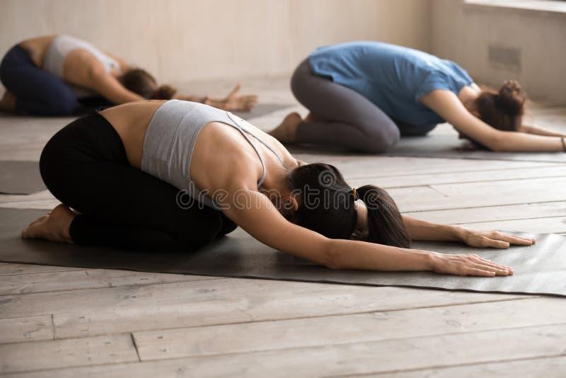 De vrouwen die kind doen stellen tijdens yoga opleiding stock fotografie
