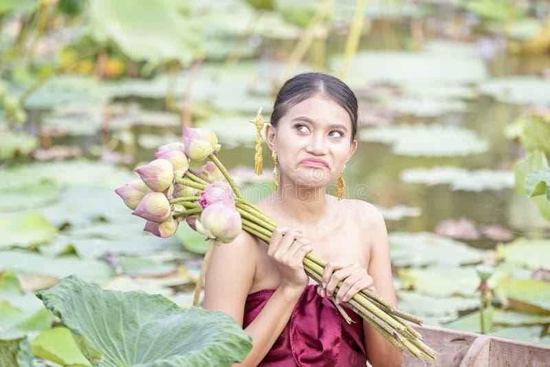 De vrouwen die Thaise kleding dragen maken jaloersheidsgezichten Aziatische vrouwen die op houten boten zitten om lotusbloem te v royalty-vrije stock foto's