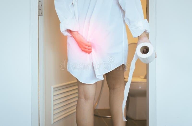 De vrouwen die toilet gebruiken en lijdt aan Diarree en Hemorroïden omhoog na kielzog in ochtend bij huis stock afbeelding