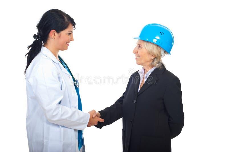 De vrouwen die van de arts en van de architect handen schudden stock afbeeldingen