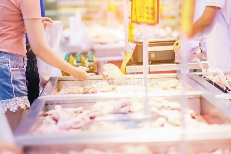 De vrouwen die Vers voedsel op de markt shoping vandaag is het vlees van kippenvleugels in een opslag royalty-vrije stock foto's