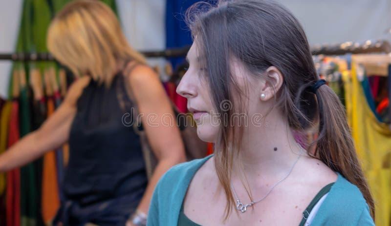 De vrouwen die voor klerenmoeder en dochter winkelen bekijken het hangen van kleren stock fotografie