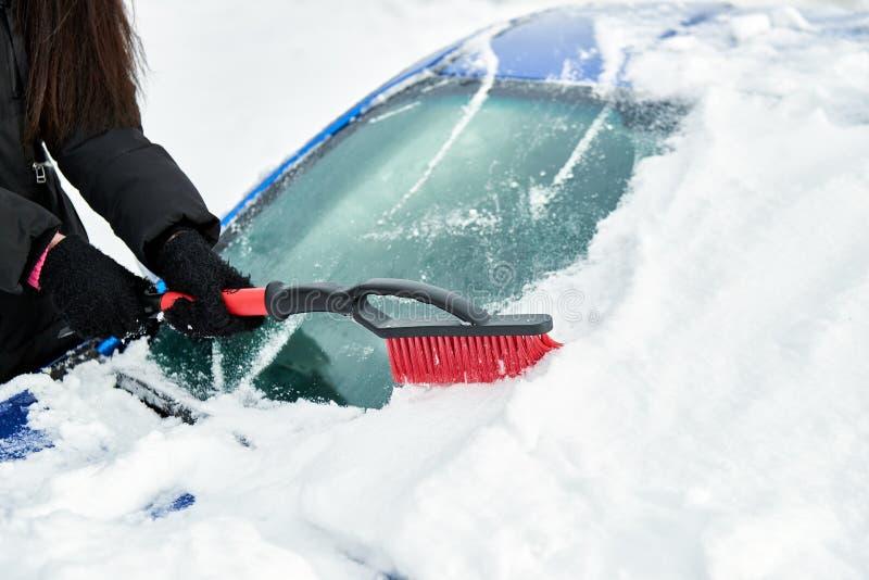 De vrouwen dienen zwarte handschoen in verwijdert sneeuw uit autowindscherm in de winterdag stock foto