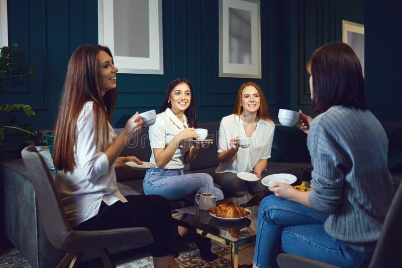 De vrouwen drinken koffie thuis lachend bij een vergadering van vrienden royalty-vrije stock afbeelding