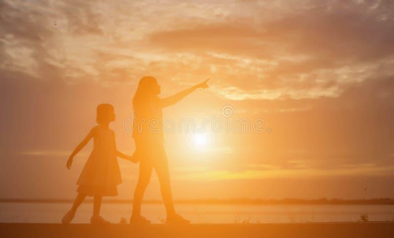 De vrouwen en de kinderen letten op de zonsondergang in de avond royalty-vrije stock afbeeldingen