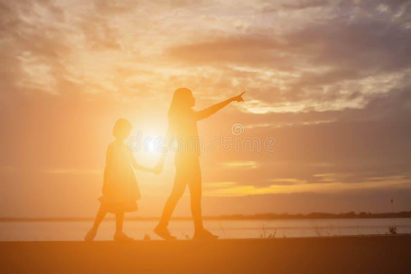 De vrouwen en de kinderen letten op de zonsondergang in de avond stock afbeelding