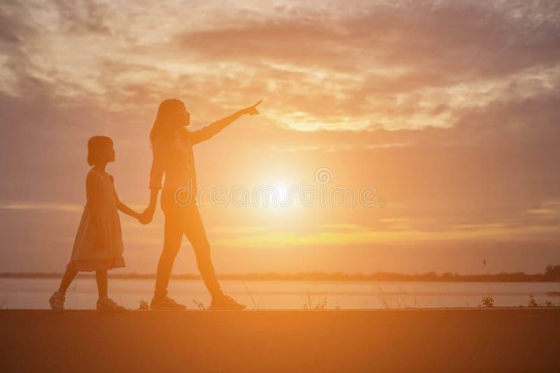 De vrouwen en de kinderen letten op de zonsondergang in de avond stock fotografie