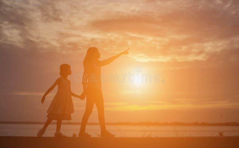 De vrouwen en de kinderen letten op de zonsondergang in de avond royalty-vrije stock fotografie