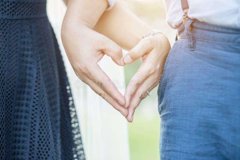De vrouwen en de man dragen een ring samen in de handen van de vingerholding royalty-vrije stock afbeeldingen