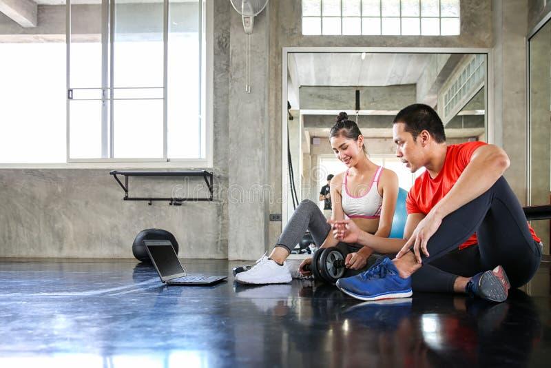 De vrouwen en de trainers analyseren oefening Jonge vrouw met persoonlijk trainer en oefeningsplan op computer in gymnastiek royalty-vrije stock afbeelding