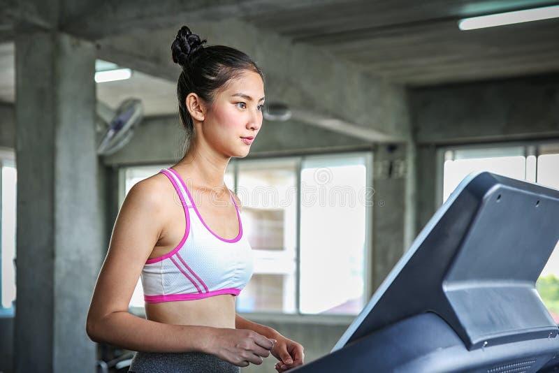 De vrouwen gaan een gewichtscontroleprogramma in Jongeren die op tredmolen lopen Jonge vrouw opleiding in de gymnastiek Mooi stock fotografie
